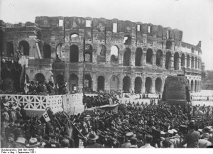 1931: Mussolini (left on the podium) addresses the fascist youth movement outside the Colosseum and the Meta Sudans.