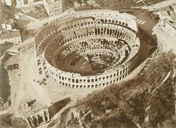 Aerial view of the valley of the Amphitheatre with the base of the Colossus of Nero, the Meta Sudans and the Arch of Constantine in a picture from about 1895.